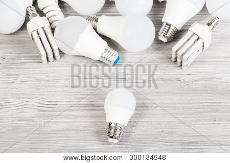 Top View Of White Led Bulb Light And Several Energy-saving Lamps On Gray Wooden Board