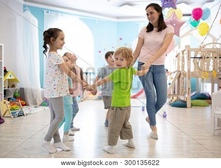 Group Of Happy Children Standing In Circle Holding Hands, Playing With Their Teacher In Daycare