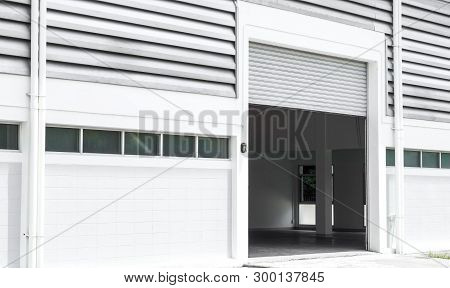 Factory Warehouse And Industrial Concept - Shutter Door And Wall Of Factory Or Warehouse Building In