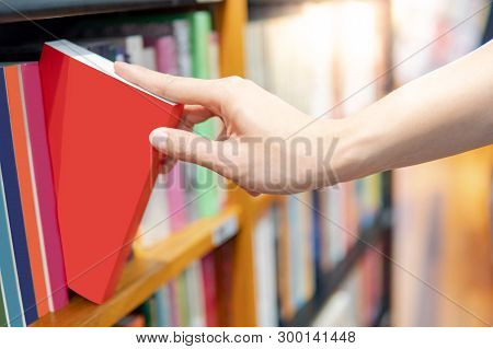 Bestseller Publishing Concept. Male Hand Choosing And Picking Red Book From Wooden Bookshelf In Book