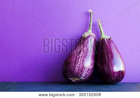 Two Ripe Purple Aubergine Eggplants On Violet Black Background. Organic Vegetables With Beautiful St
