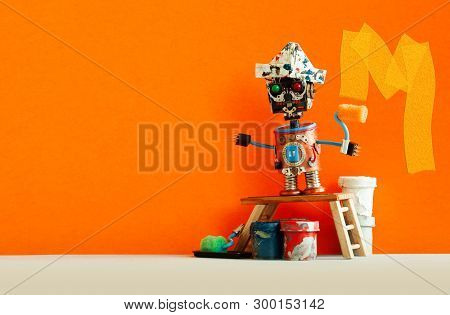 Funny Decorator Robot Repaints The Wall Of The Room Orange Color. Creative Painter Robot Toy, Wooden