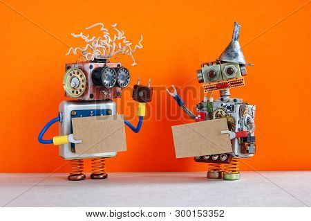 Two Comical Robots With A Cardboards Mockup. Creative Design Robotic Toys Holding A Blank Empty Pape