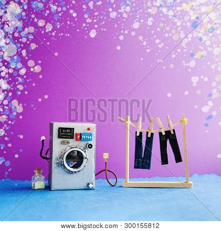 Washing Machine With Laundry, Mens Jeans Pants Dried On Clothesline With Clothespins. Purple Wall In