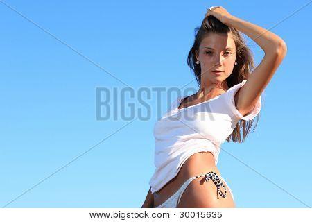 Beautiful young sexy bikini model by the sea