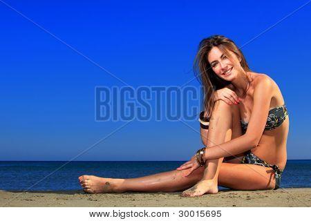 Beautiful girl laying on the beach enjoying the Ionian sea in Greece