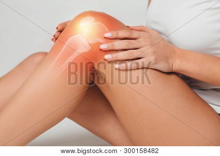 Woman Wearing Sports Clothes Suffering From Pain In Knee. Close-up Painful Knee With Bones