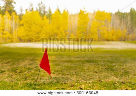 Red Flag On Rough Next To Green Golf Course In Autumn Mountain Area