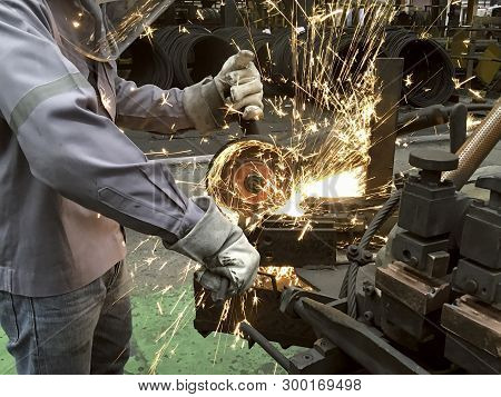 Worker In Factory, Welding And Grinding Steel Wire, Flash Of Fire From Grinding Stone, Metal Industr
