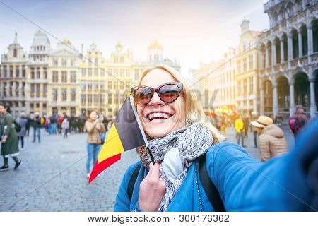 Young Woman Tourist Stands With The Flag Of Belgium On The Background Of The Grand-place Or The Gran