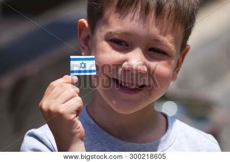 Happy Israeli Caucasian Jewish Child With A Tiny Flag Of Israel In His Hands. Israeli Kid Celebratio