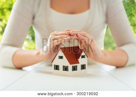 security and home insurance concept - close up of woman protecting house model by hands over green natural background