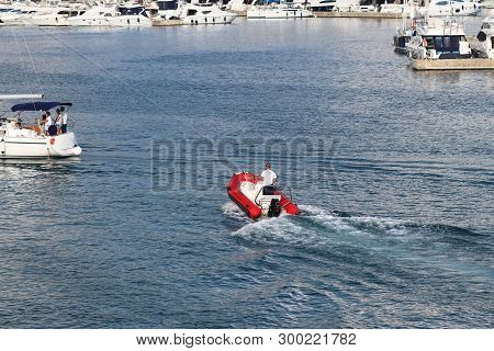 The Marina Staf Is Sailing On A Red Inflatable Motorboat To A Sailing Cruise Yacht Entering The Mari