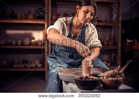 Beautiful Ceramist Sculptor Works With Clay On A Potters Wheel And At The Table With The Tools. Craf