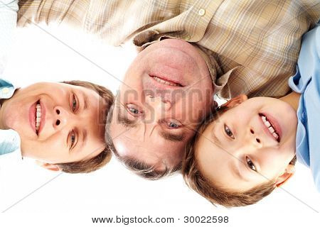 Multigenerational portrait of male members of the family smiling and looking down at camera