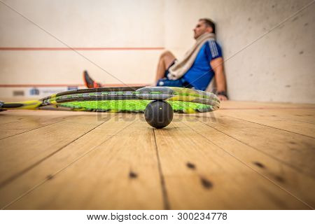 A Man Resting Against The Side Wall After A Very Hard Game Of Squash
