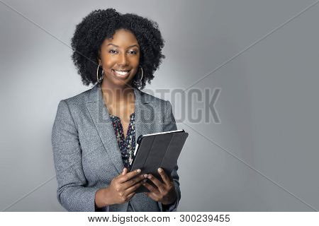 Black African American Teacher Or Businesswoman Sitting And Holding A Tablet Computer.  The Confiden