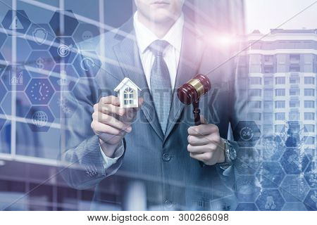 A Closeup Of A Man Holding A Hammer And A House Model With Total Legal System Structure At Busy City