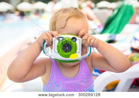 Happy little girl making photos by taoy camera on summer holidays
