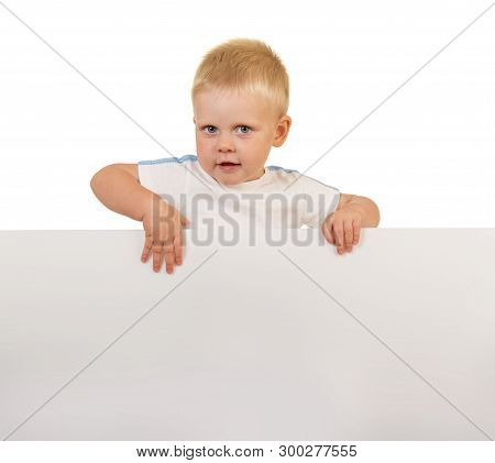 Smiling Little Boy With Piercing Eyes Behind A White Blank Banner Isolated On White Background