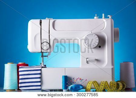 Modern White Electric Sewing Machine With Accessories For Needlework On A Blue Background