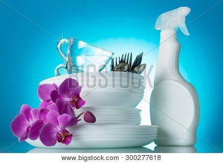 Clean The Dinner Dishes Are Stacked, The Tool From Dirt, Orchid Flower On Bright Blue Background