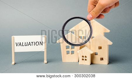 A Poster With The Word Valuation And A Miniature Wooden House. Real Estate Appraisal. Rate The Prope