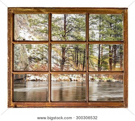 mountain river canyon in early spring after snowstorm as seen through a vintage sahs window