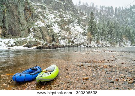inflatable whitewater kayak and packraft on a shore of mountain river in heavy springtime snowstorm - Poudre River in northern Colorado
