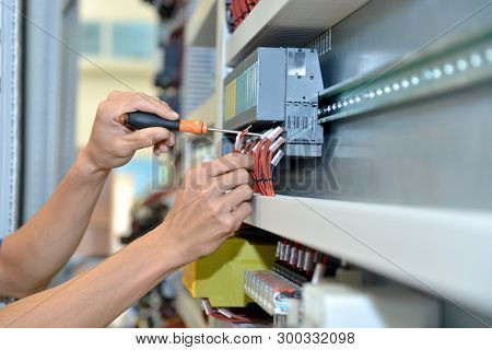 The Electrician Is Connecting The Electric Cable Wire. Engineer Maintenance And Fix The System Contr
