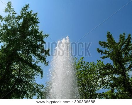 Water Pillar With A Splash From A Drop Against The Background Of Blue Sky And Green Trees, Bottom Vi