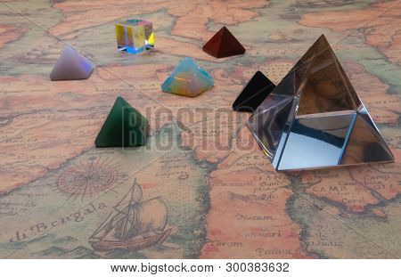 Crystal Pyramide And Small Pyramids Of Natural Gemstones With Light Cube On An Ancient World Map. Ga