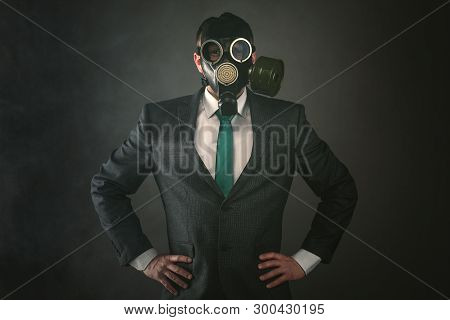 Disgruntled man in a gas mask and suit on a gray background. Pollution of environment concept. poster