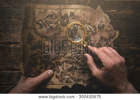 Traveler Is Looking On An Old Map In His Hands Through A Magnifying Glass. Treasure Hunt Concept.o