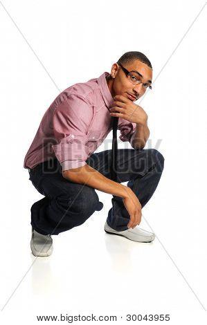 Retrato de jovem americano africano, agachando-se com a mão no queixo isolado sobre fundo branco