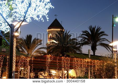 Christmas Decorations In A Plaza With The Carmen Church Bell Tower (parroquia Nuestra Senora Del Car