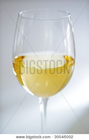 Glass of white wine against white background with soft focus