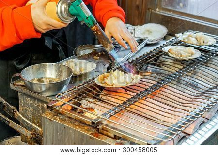 Hand Of Chef Using Burner Cooking And Burn Big Scallops Shells With Cheese On Stove To Sale For Cust