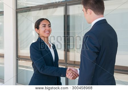 Smiling Ambitious Business Woman Saying Good Bye To Partner. Young Man And Woman In Formal Suits Sha