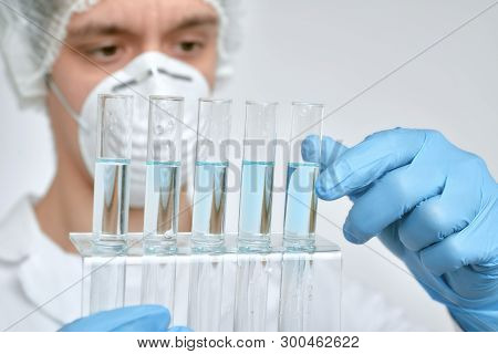 Keen Scientist In Protective Wear Performs Protein Assay. Shallow Dof, Focus On The Tubes And Gloved