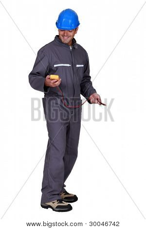A tradesman holding a multimeter poster