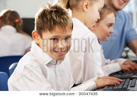 Boy in school class smiling to camera