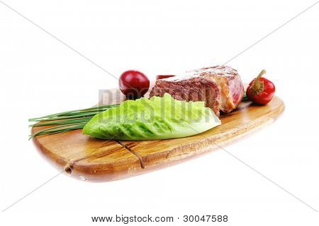 meat savory : beef fillet mignon grilled and garnished with green lettuce and red chili hot pepper on wooden plate isolated over white background