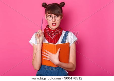 Creative Cute Schoolgirl Stands Isolated Over Pink Background In Studio, Opens Her Mouth And Eyes Wi