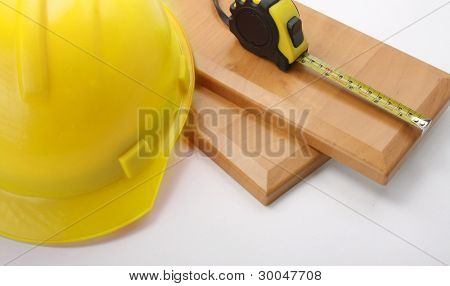 An orange hardhat with a ruler on wooden planks