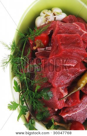 uncooked fresh beef meat chunks on ceramic bowls with vegetables and red peppers isolated over white background