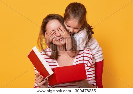 Image Of Little Cute Daughter Closing Eyes Of Mommy, Woman Holding Red Gift Box While Sitting On Flo
