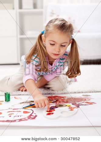 Little girl painting with finger sitting on the floor