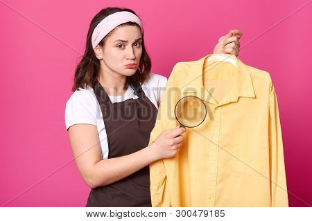 Brunette Housewife Holds Yellow Shirt After Laundry With Coffee Stain On Fabric, Having Magnifying G