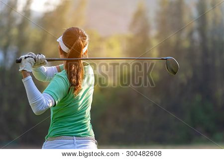 Sport Healthy. Asian Sporty Woman Golf Player Doing Golf Swing Tee Off On The Green Sunset Evening T